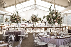 wedding reception tent lavender purple table acrylic chairs greenery pink flowers chandeliers