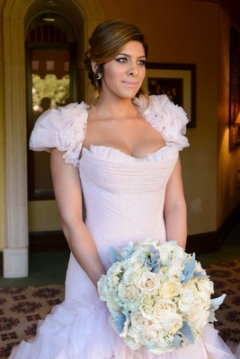 Bride in blush pink wedding dress with ruffle bolero and skirt carries white and ivory rose bouquet