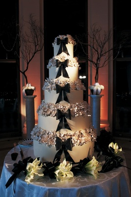 Black bow and sugar flowers on tall wedding cake