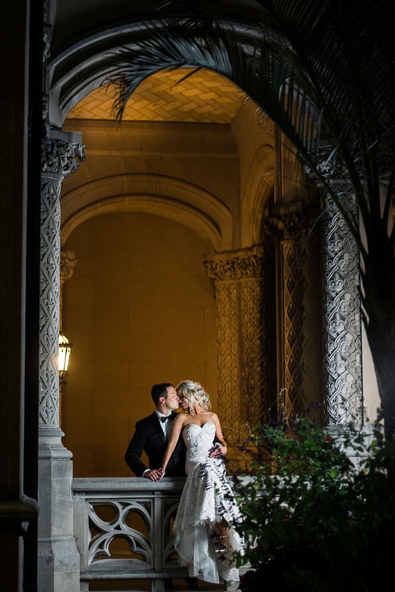 Wedding portrait photography couple photo bride sitting on railing groom kisses from behind her