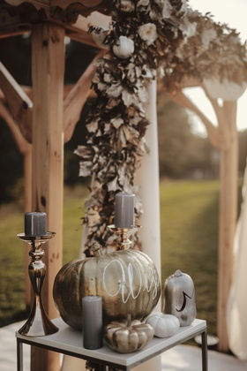 fall wedding ideas wood ceremony arbor gold leaves white flowers grey candles pumpkins gold white