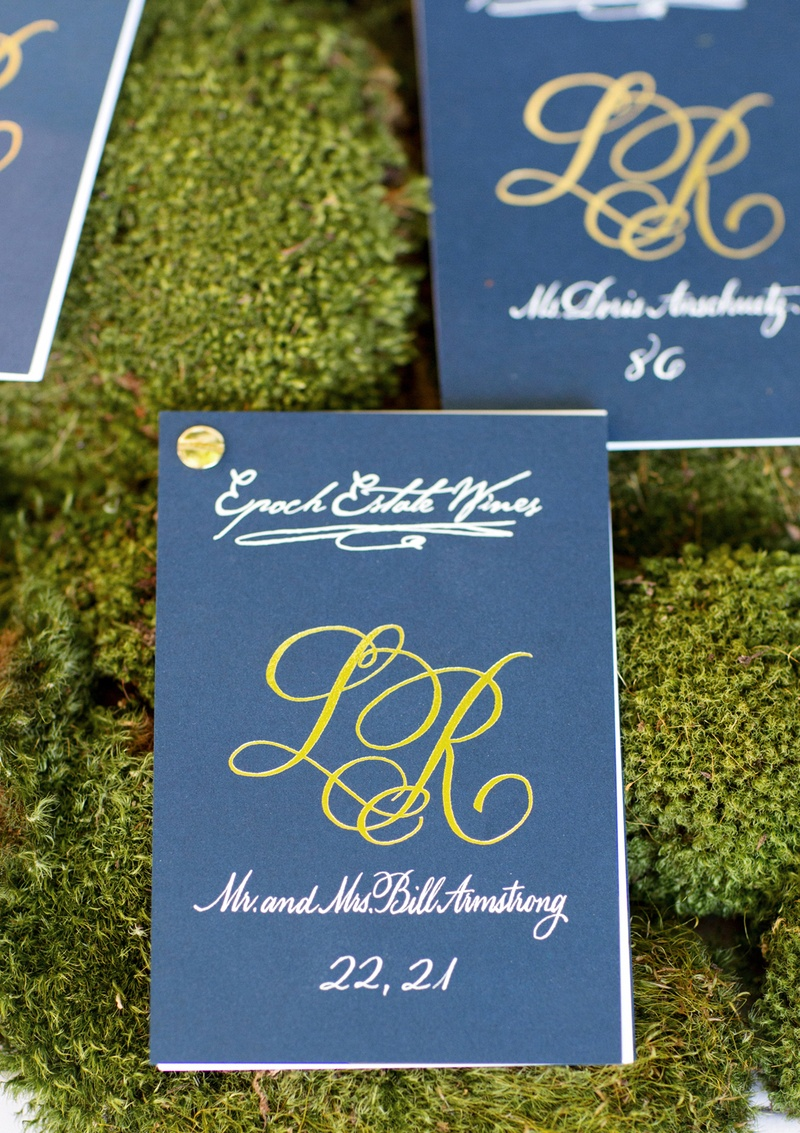 Blue and green seating cards with gold pin