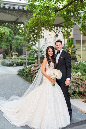 bride in fit and flare trumpet gown groom in black tuxedo garden courtyard smiling