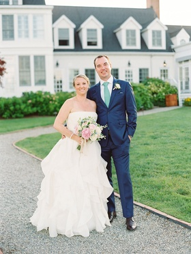 Bride in strapless wedding dress pink bouquet with groom navy blue suit with green tie