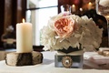 Wedding reception table with small centerpiece of white flowers with a peach bloom in a frosted vase