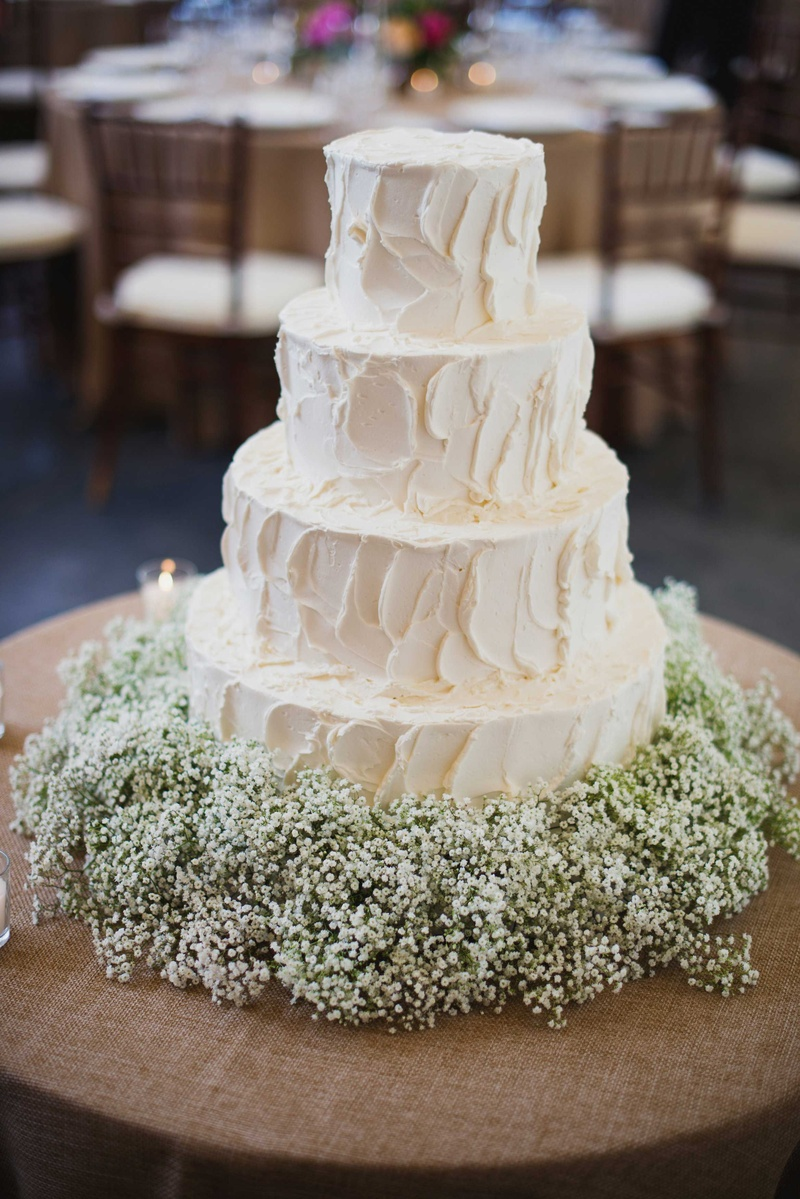 Simple White Four Layer Wedding Cake With Baby S Breath Flowers At Base