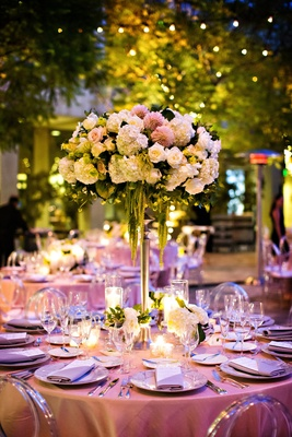 Tall wedding centerpiece round table clear chairs pink dahlia white hydrangea rose amaranthus