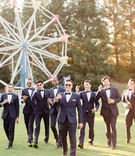 groom and groomsmen in midnight blue tuxedos in front of ferris wheel with flask and cigars