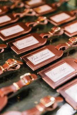 embossed leather luggage tags in calligraphy as escort cards and favors