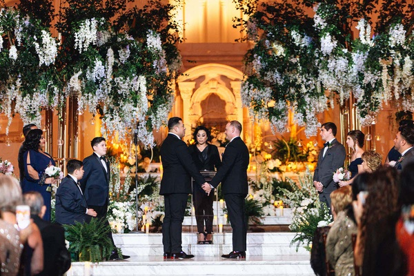 same-sex wedding inspiration, two grooms exchanging vows at vibiana, large floral display