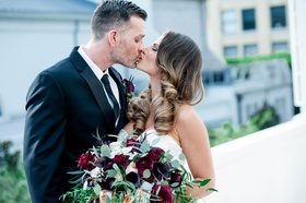 Bride in strapless wedding dress kissing groom hair in curls burgundy and greenery bouquet