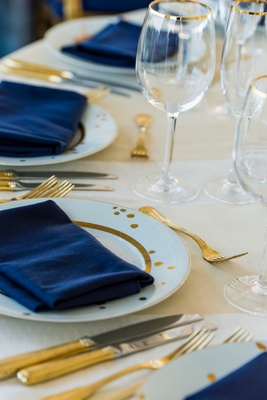 Gold-rimmed glassware and gilt flatware on ivory table