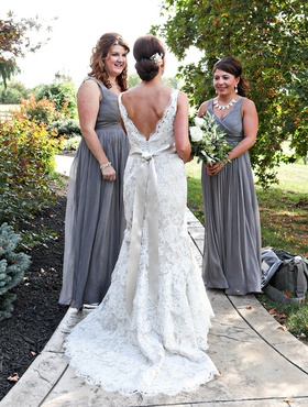 Bride in Alvina Valenta lace gown with V-back, satin sash, chapel train, bridesmaids in J.Crew