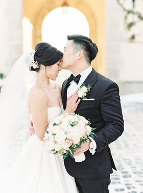 chinese american couple kiss forehead oheka castle wedding winter snow on ground strapless dress