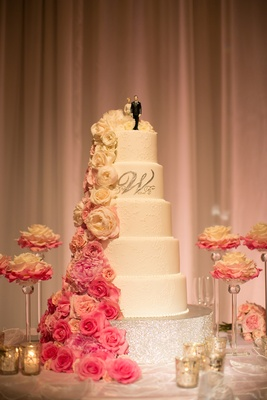 White wedding cake with silver monogram and fresh cascading flowers