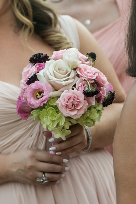 Bridesmaid holding pink, green, and white flowers