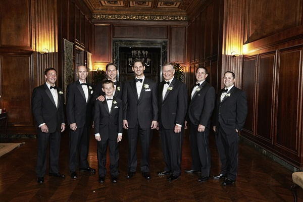 Men in black tuxedos and bow ties in wood room