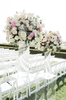 wedding ceremony grass lawn white chairs acrylic lucite riser tall flower arrangements