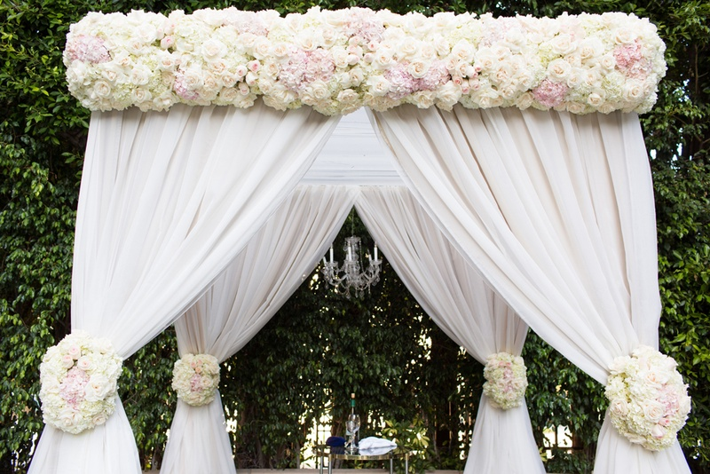 chuppah with blush and ivory flowers and white drapery