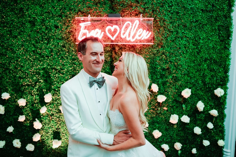 groom in white tuxedo hugging bride in strapless dress underneath neon sign with names on boxwood