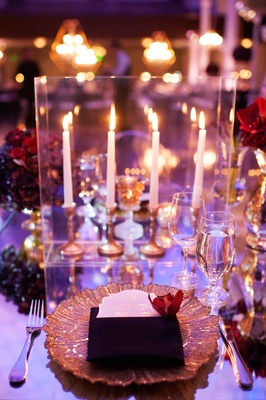 Guest place setting with gold charger on mirror table with red centerpiece and taper candlesticks