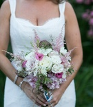 Bride holding white and pink bouquet with foliage