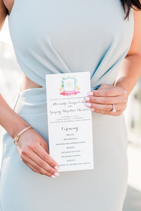 wedding guest in light blue dress with side cutouts holding wedding ceremony program tropical crest