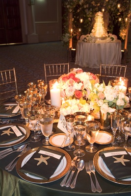 Table with gilded glassware and rose centerpieces
