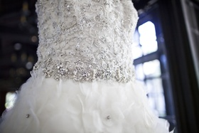Lazaro wedding dress with bodice covered in beading, crystals, sequins, ruffled skirt with crystals