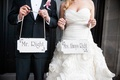 Bride and groom holding personalized wood signs