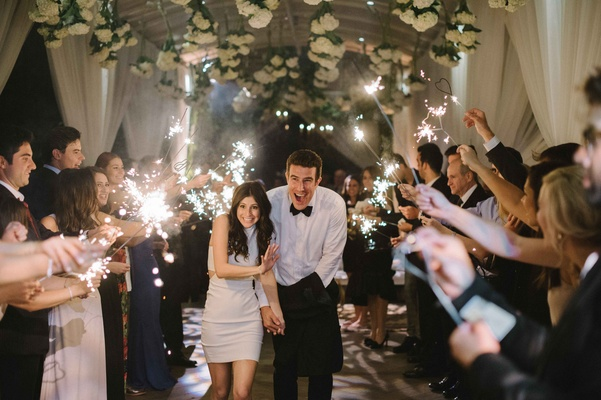 Bride in second wedding dress with groom running through tunnel during sparkler exit Beverly Hills