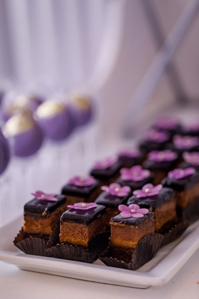 Chocolate ganache bite size wedding reception dessert with edible purple flower decoration pearl dot