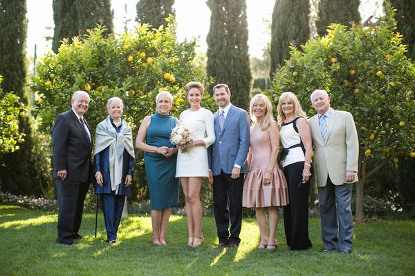 Bride in a mini Mod dress, groom in blue blazer, black pants with guests in San Ysidro Ranch garden