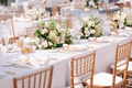 long king's table with white linen low centerpiece gold back chairs peach accent color candle votive