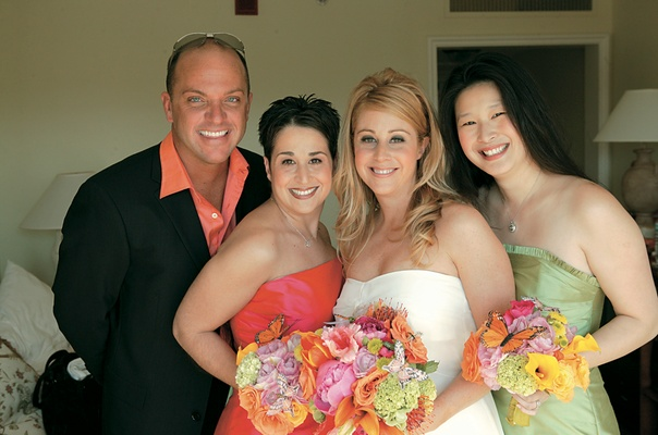 bride and bridesmaids carry brightly colored bouquets