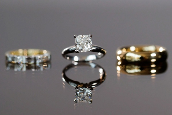 Bride's solitaire engagement ring four prong with wedding ring and groom's gold band