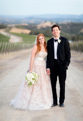 Redhead bride in blush gown and tuxedo groom