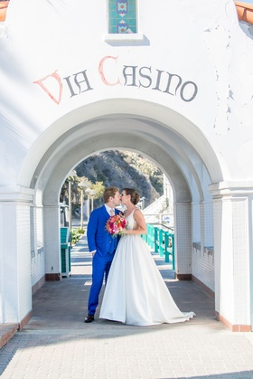 bride and groom kiss under arch in beach wedding