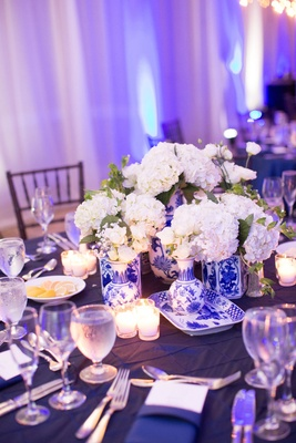 Navy blue wedding linen blue uplighting reception decor blue white vase with white flowers in center