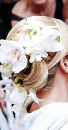 Blonde updo with white orchid hair accessory