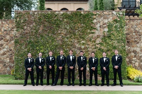 Groom and groomsmen in front of ivy wall