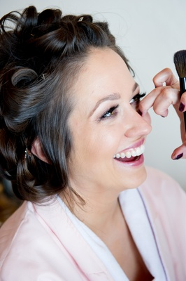 Woman putting bridal makeup on girl in curlers