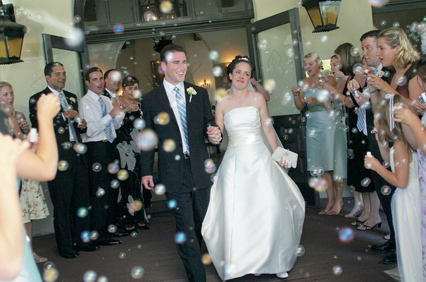 Bride and groom walk through bubbles during grand exit