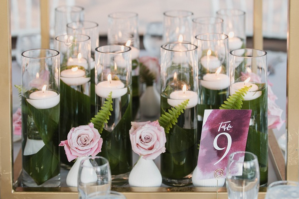 base of centerpiece, collection of floating candles with leaves wrapping hurricanes