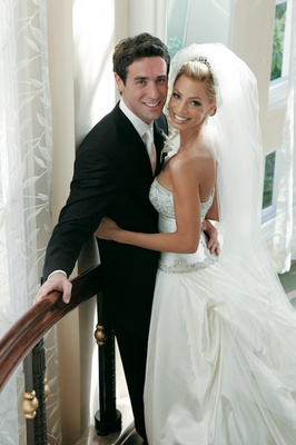 Bride in a veil and gown with a beaded bodice and pickup skirt, and groom in a black tuxedo