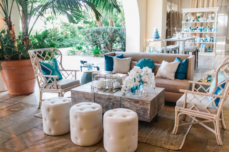 Wedding reception lounge for cocktail hour with blue pillows, orchids, tufted ottoman pouf, rattan