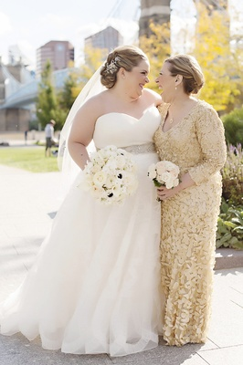 bride in strapless sweetheart watters wedding dress, mother of the bride in gold theia dress