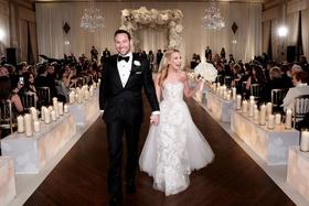 Bride in strapless mira zwillinger wedding dress with overskirt groom tuxedo flower boxes aisle