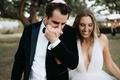 groom in tuxedo bow tie yarmulke kissing wife's hand after ceremony v neck wedding dress