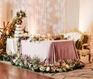 wedding reception ballroom sweetheart table gold antique settee purple linen greenery driftwood cake